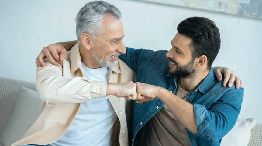 Cheerful retired man fist bumping with happy bearded son at home | Male Menopause Is A Real Thing | FAQs and Solutions | loss of libido | Featured