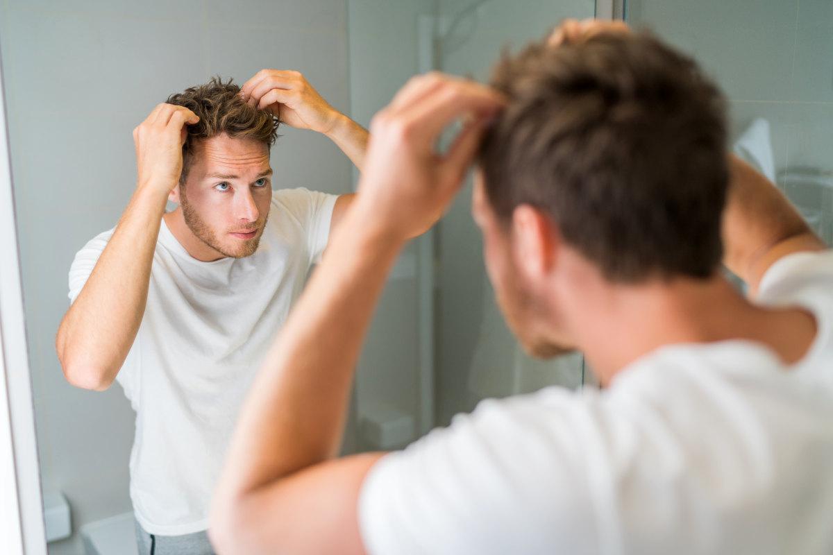 Hair loss man looking in bathroom mirror | Finasteride FAQ: How To Prevent Hair Loss, Side Effects, Uses | oral finasteride