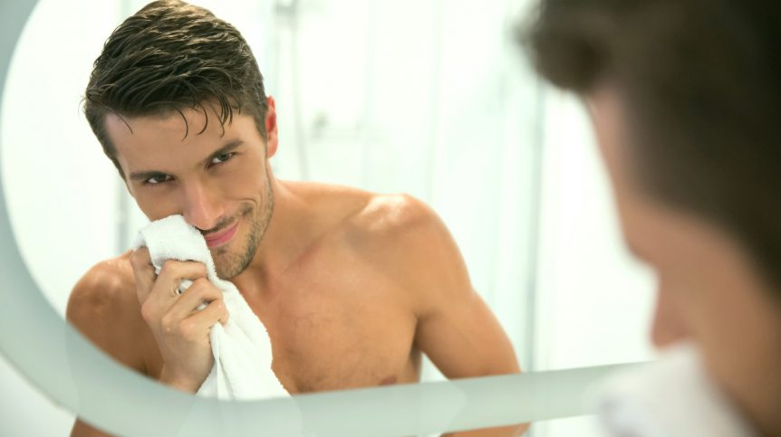 Man with towel looking at his reflection in the mirror in bathroom   Grooming Tips To Make Your Hair Look Thicker and Fuller   haircuts to make hair look thicker   Featured