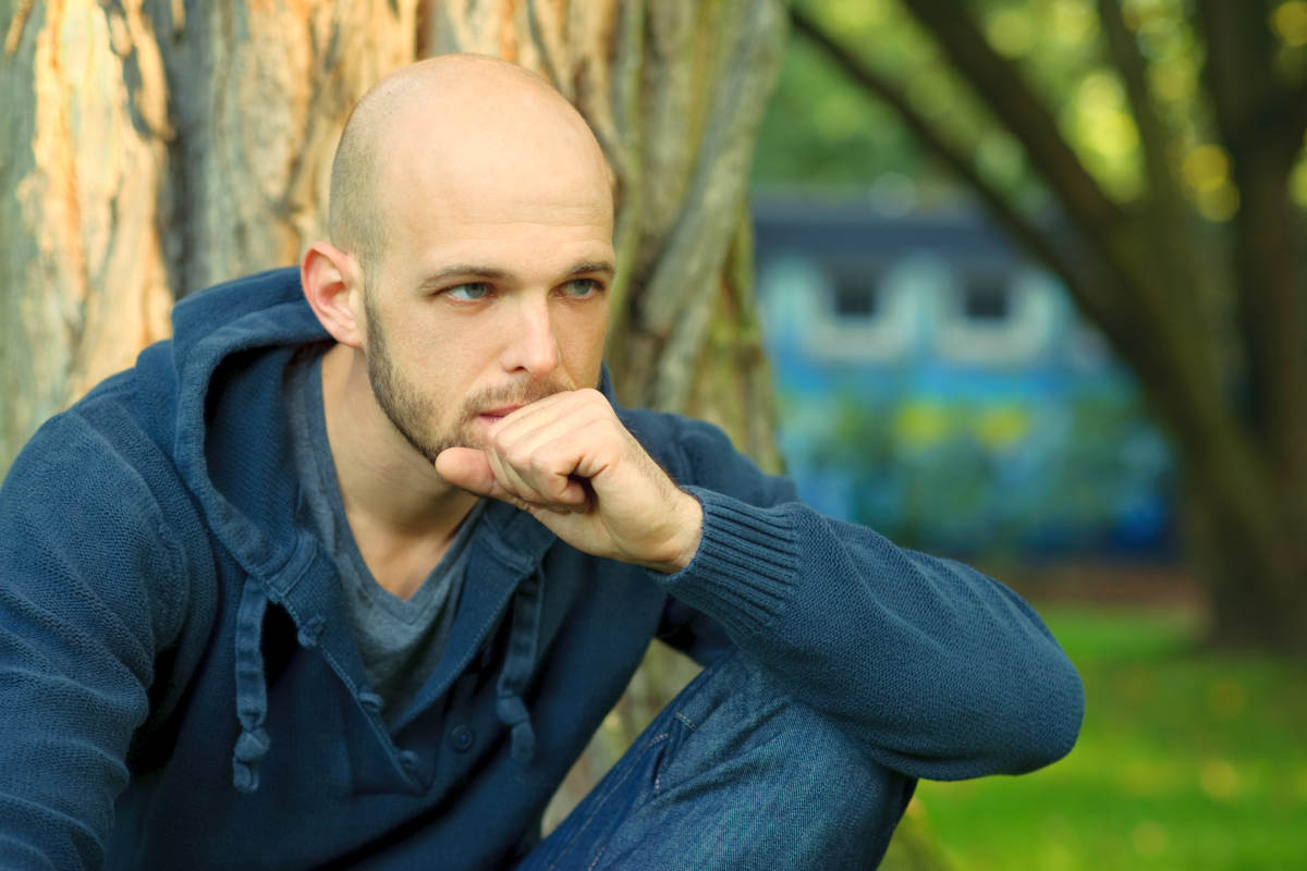 Portrait of young man sitting in park and thinking | Male Pattern Baldness: Which Stage Are You In? | hair loss cure