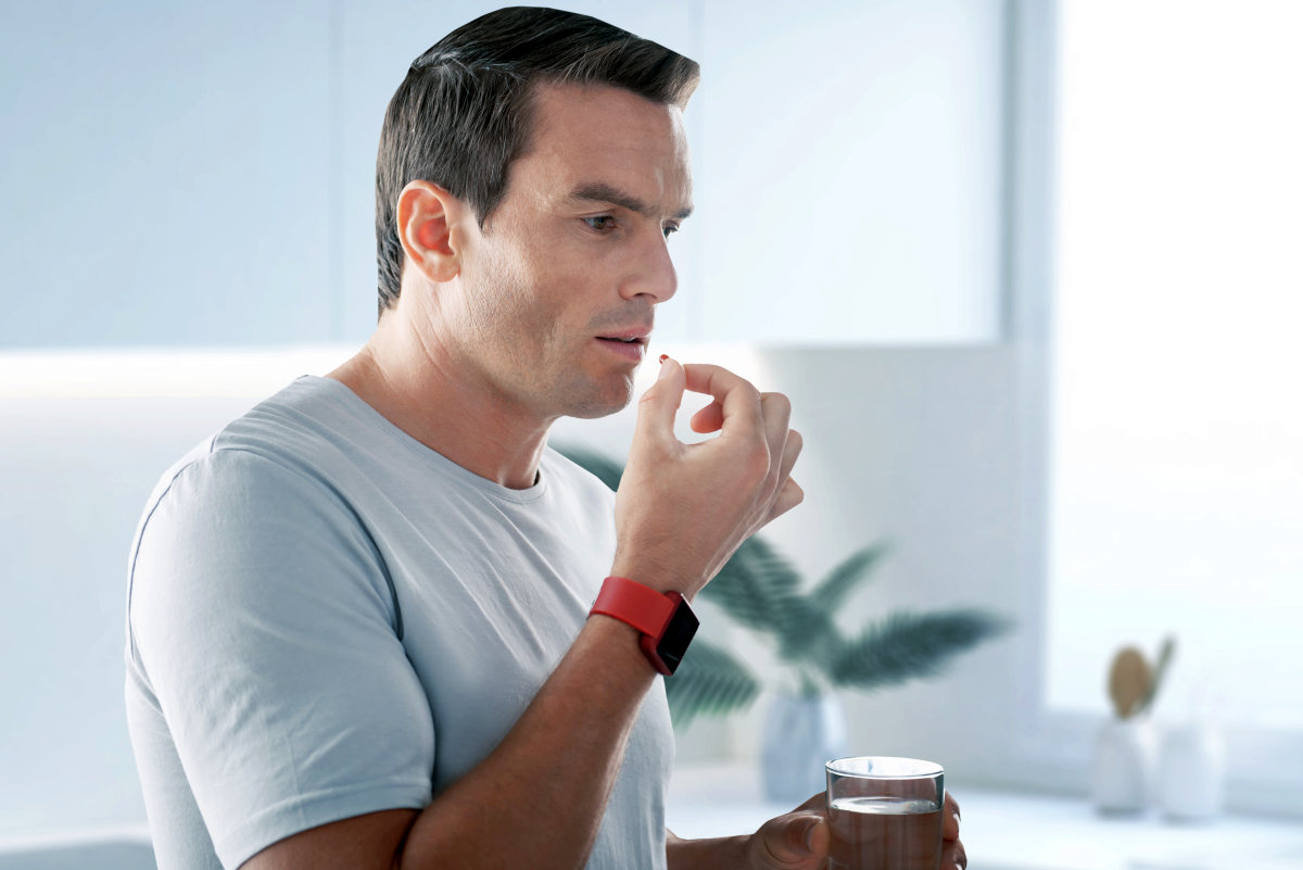 Handsome young man standing with a glass of water and taking pills | Tadalafil FAQ: How Long The Daily ED Pill Lasts (And Common Questions) | tadalafil dosage