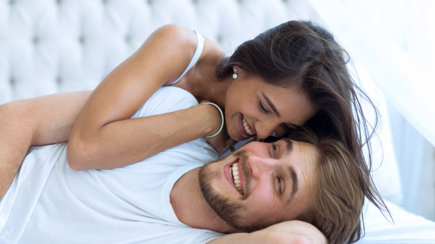 Young happy couple lying together in bed | Priapus Shot To Treat ED? When More Men Are Choosing The P Shot | increase penis sensitivity | Featured