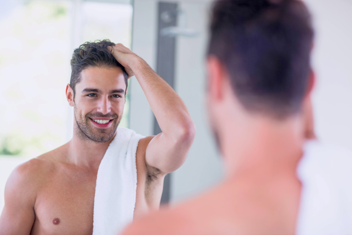 Handsome shirtless man looking in the mirror in the bathroom | Can DHT Blockers Stop Hair Loss? | natural dht blocker
