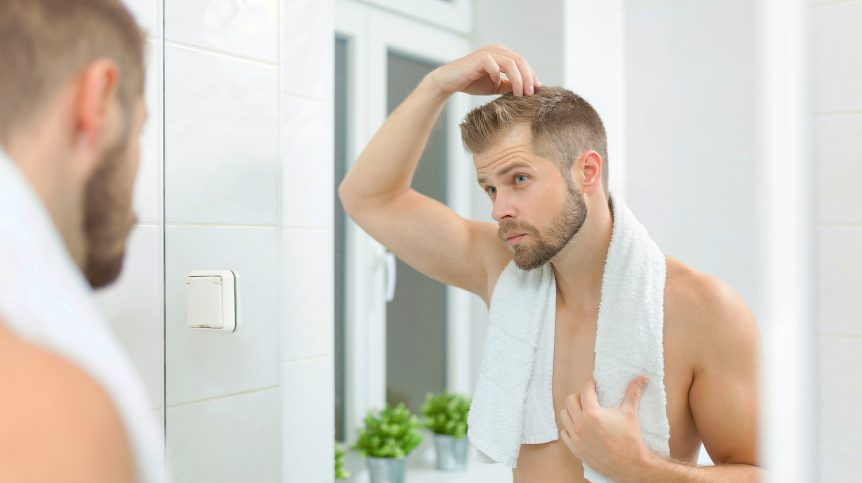 Handsome unshaven man looking into the mirror in bathroom   Tips & Tricks To Deal With Receding Hairline In Men   receding hairline treatment   Featured
